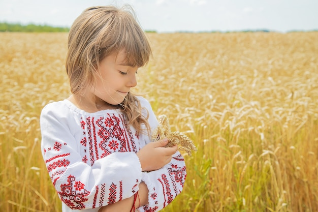A child in a field of wheat in an embroidered shirt.