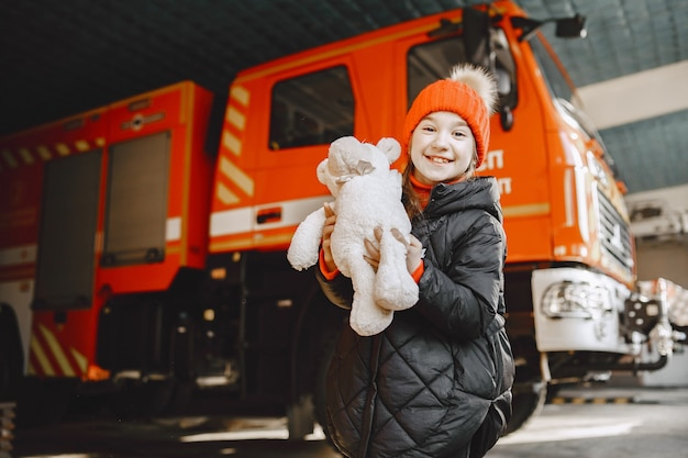 Child in  fire station. girl with a toy. child near fire truck.