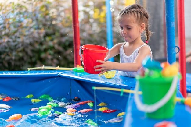 Ребенок-рыбак ловит пластиковую игрушку рыба в бассейне парк развлечений летний день маленькая девочка развлекается на рыбалке карнавал фестиваль развлечения для детей