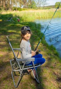 A child on a fishing trip is catching fish in the summer