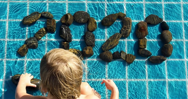Child folds the inscription 2020 from the stones sitting in the pool top view