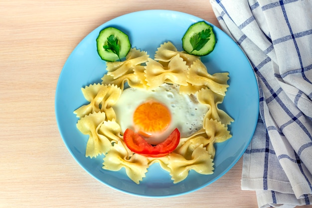 Детская еда. смешная еда. тарелка с макаронами с жареным яйцом и овощами в виде смешное лицо. детское меню и концепция обеда.