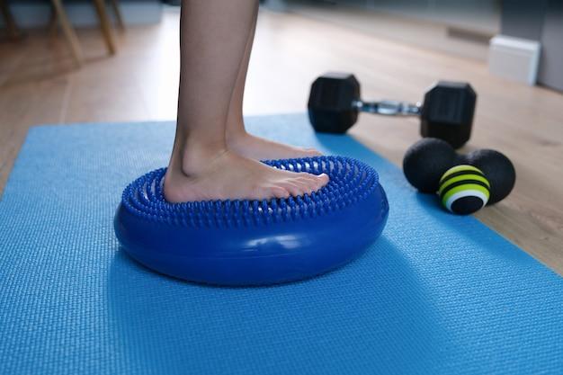Child foot is resting on blue massage balancing cushion closeup
