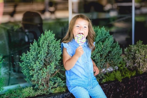 Ребенок на прогулке в парке с конфетой в руке