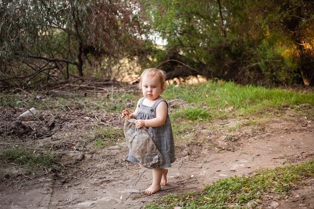 子供は森の中にゴミ箱を見つけました。環境、自然を守ります。