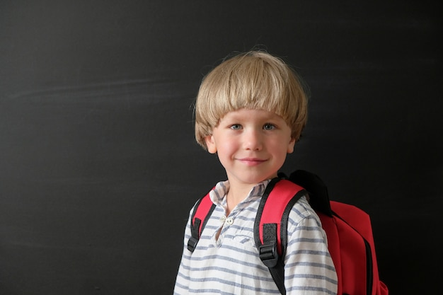 Child from elementary school with bag at blackboard.
