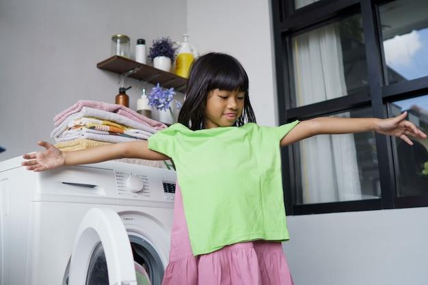 Ребенок веселится счастливая маленькая девочка, чтобы стирать одежду и смеется в прачечной