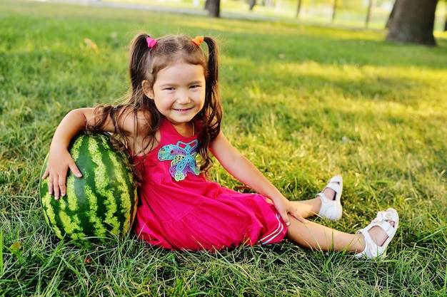 Child funny little asian girl leaning on a huge watermelon in the park on the grass
