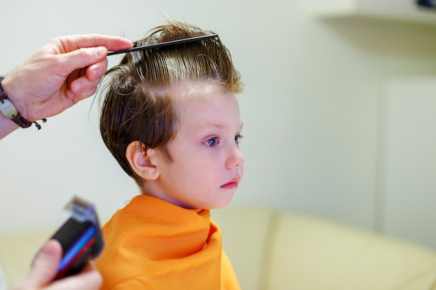 Child getting haircut at the hairdresser salon