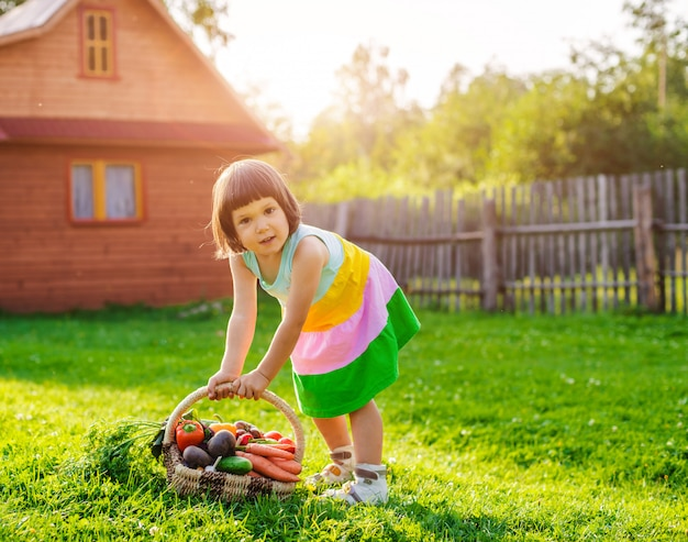 Child girl 3 years old sitting on a stone against a wooden house with a large basket full of vegetables grown in his ecological garden.