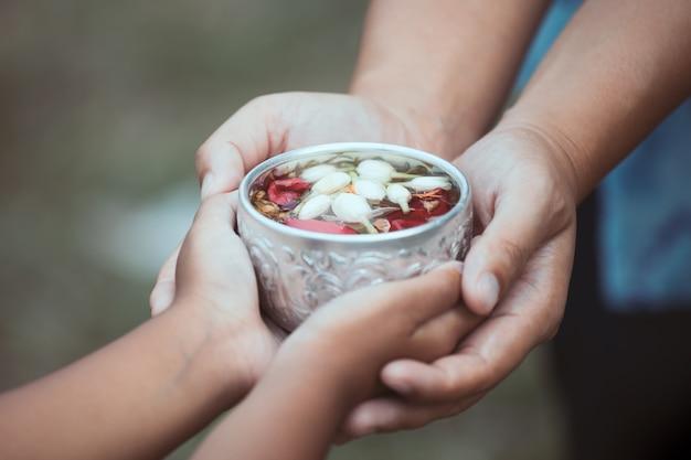 Девочка и мать, держащая чашу, у которой есть цветок лист в воде для наливания в руках