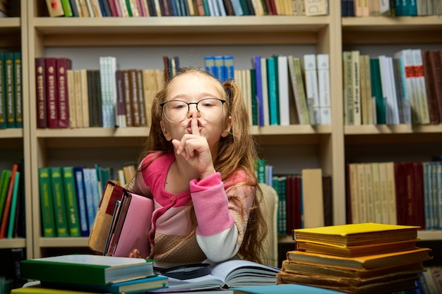 Child girl asks to be quiet in library, school child sits alone at table with books, holding one finger on mouth, keep silence concept