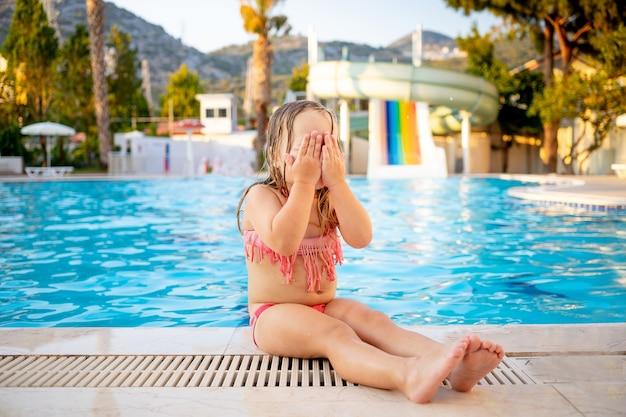 워터 슬라이드가 있는 수영장에 있는 어린 소녀는 놀람, 레크리에이션 및 여행의 개념을 예상하여 손으로 얼굴을 가렸습니다.