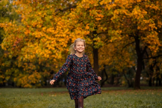 Child girl in autumn in the park runs
