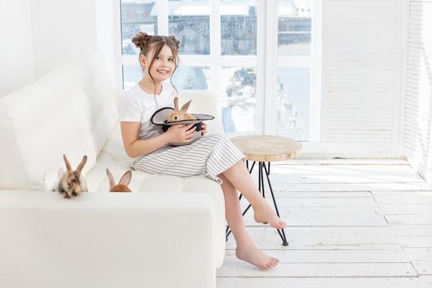 家で帽子をかぶった動物のウサギと一緒にソファに座って美しく幸せな子供の女の子