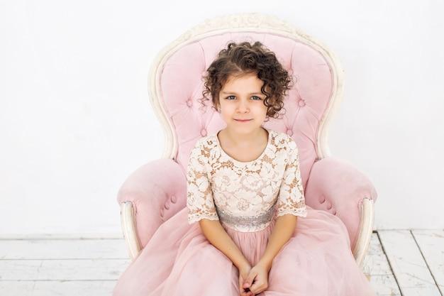 Ребенок девочка красивая, милая веселая и счастливая на розовом стуле в модном роскошном платье