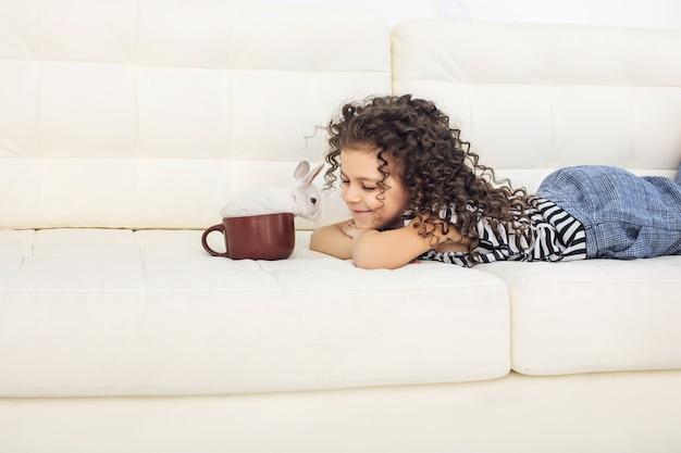 自宅のマグカップで小動物うさぎと陽気で幸せな子少女美しいかわいい