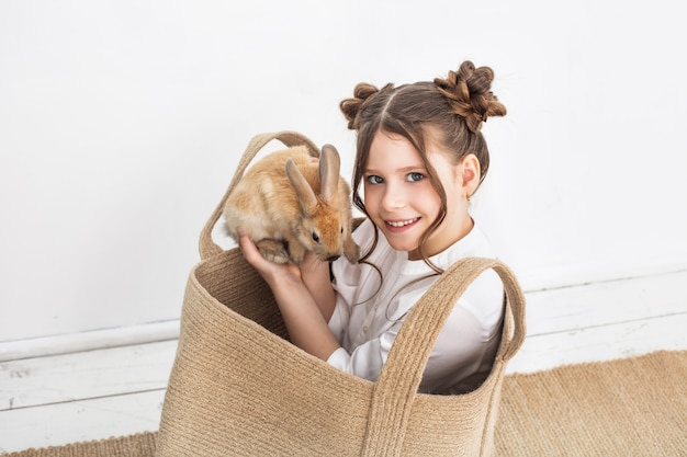 Child girl beautiful cute cheerful and happy in a wicker bag with small animals rabbits