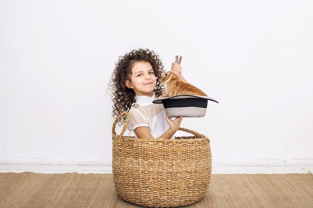 Child girl beautiful cute cheerful and happy in a wicker basket with small animals rabbit in a hat