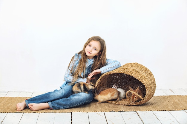 Child girl beautiful cute cheerful and happy with little animals rabbits on white wall background