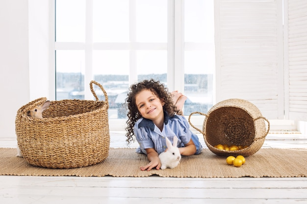 Child girl beautiful cute cheerful and happy with small animals rabbit and easter eggs at home