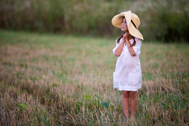 Child girl in big straw hat.