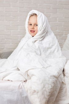 Child girl in blanket sitting on bed
