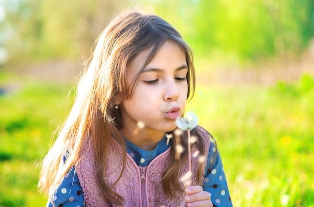 Девочка дует одуванчик весной