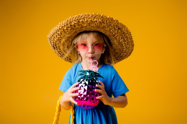 Child girl in a blue dress is holding a pineapple-shaped drink glass on a yellow background