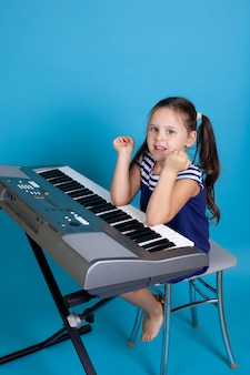 Child girl in a blue dress sits on a chair and plays the piano with her elbows