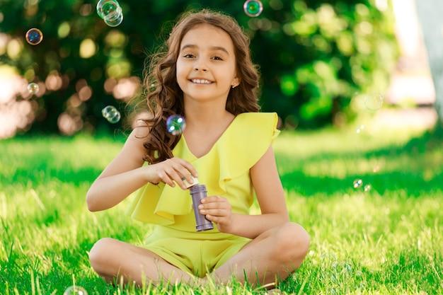 Брюнетка девушка ребенка с темными волосами сидит на траве в парке и пускает пузыри. фото высокого качества