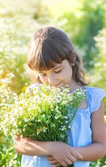 Child girl in a camomile field