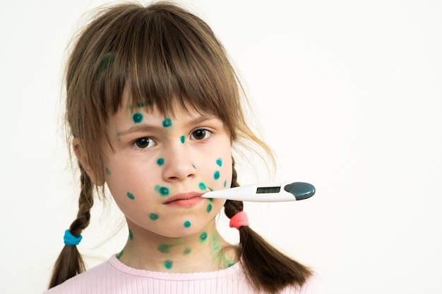 Child girl covered with green rashes on face ill with chickenpox, measles or rubella virus holding medical thermometer in her mouth having high temperature with fever.