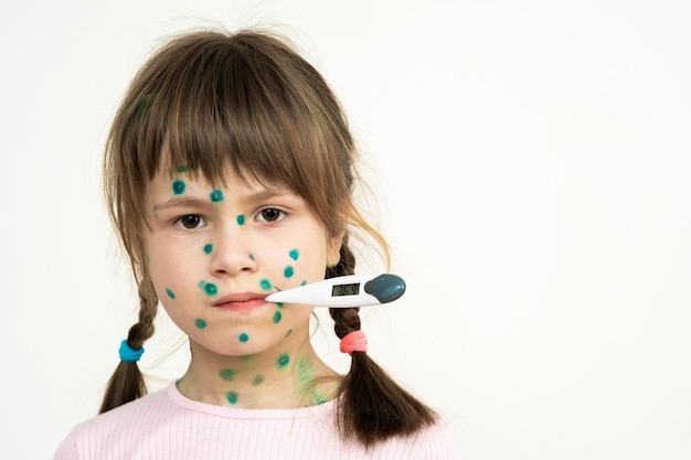 Child girl covered with green rashes on face ill with chickenpox, measles or rubella virus holding medical thermometer in her mouth