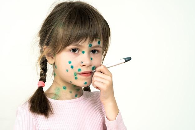 수두, 홍역 또는 풍진 바이러스로 아픈 얼굴에 녹색 발진으로 덮여있는 어린 소녀는 발열이 높은 입에 의료 온도계를 들고 있습니다.