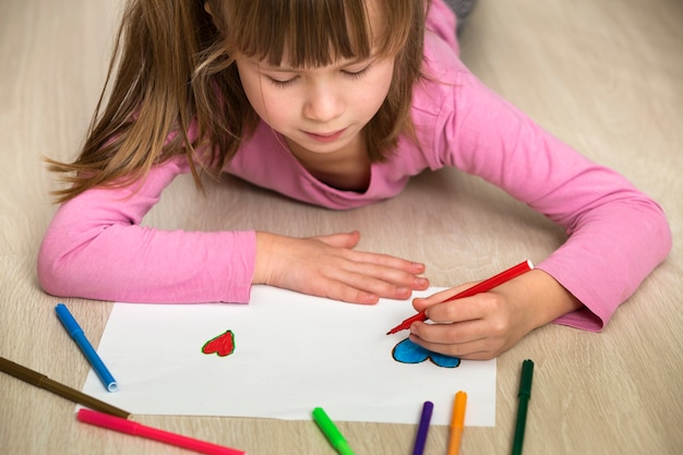 Child girl drawing with colorful pencils