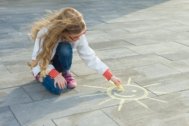 Child girl draws the symbol of the sun with colored crayons on the asphalt.