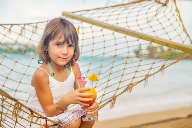 Child girl drinks cocktail on the beach.