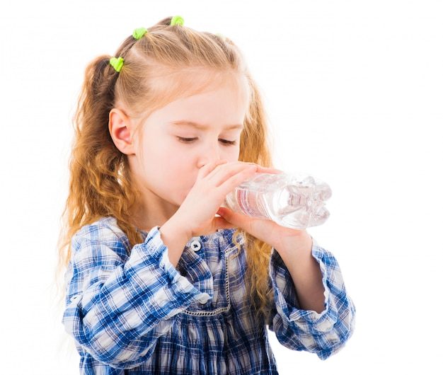 Child girl drinks mineral water from bottle