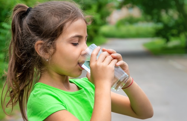 子供の女の子はグラスから水を飲みます。セレクティブフォーカス。キッド。