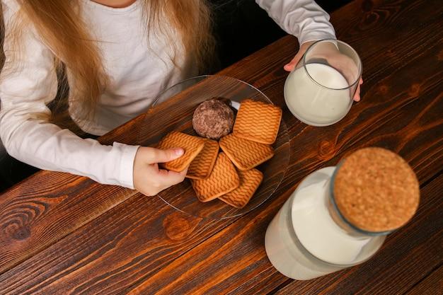 クッキーとミルクと一緒に朝食を食べる子供の女の子。成長期の子供のための健康的な毎日の朝食カルシウム