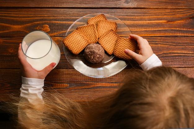 クッキーとミルクと一緒に朝食を食べる子供の女の子。成長期の子供のための健康的な毎日の朝食カルシウム。