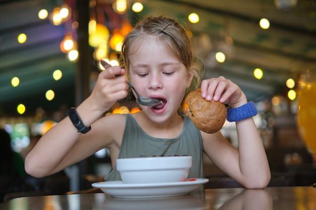 Девушка ребенка ест суп и вкусный гамбургер в ресторане.