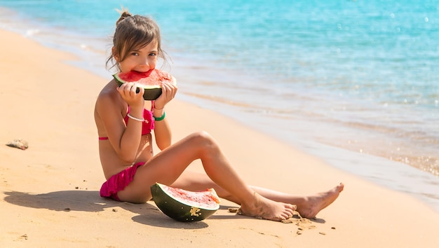 Child girl eats watermelon by the sea