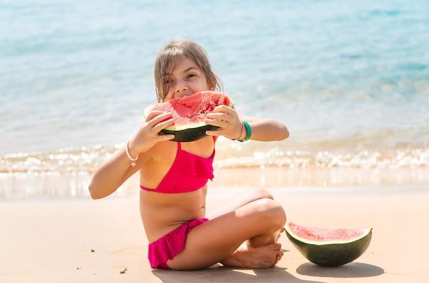 子供の女の子は海でスイカを食べる