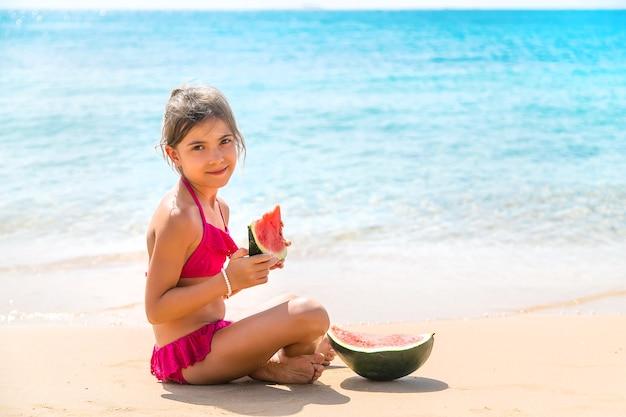 子供の女の子は海でスイカを食べる Premium写真