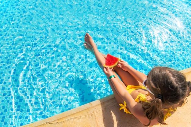 Child girl eats watermelon near the pool