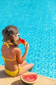 子供の女の子はプールの近くでスイカを食べる Premium写真