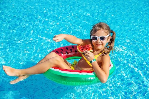 子供の女の子はプールの近くでスイカを食べる