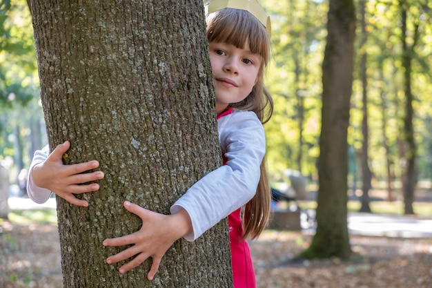 Child girl embracing a tree trunk in the park